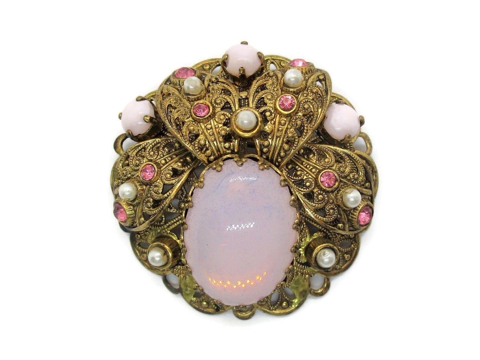 Gold brooch. The pink glass cabochon is the main feature. It is surrounded by gold embellishments, similar to a headdress. There are mini pink and beige colored pearls amongst the gold.