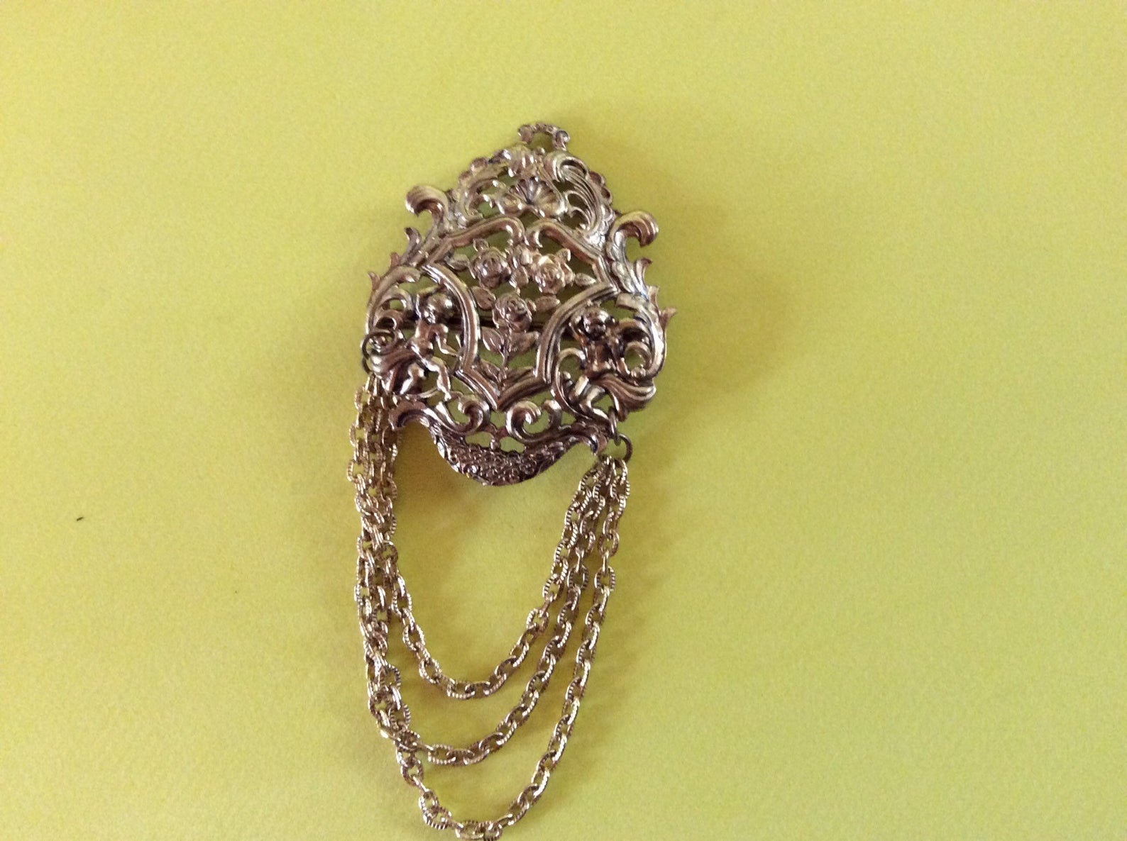Gold brooch. Regal emblem with chains hanging off it.