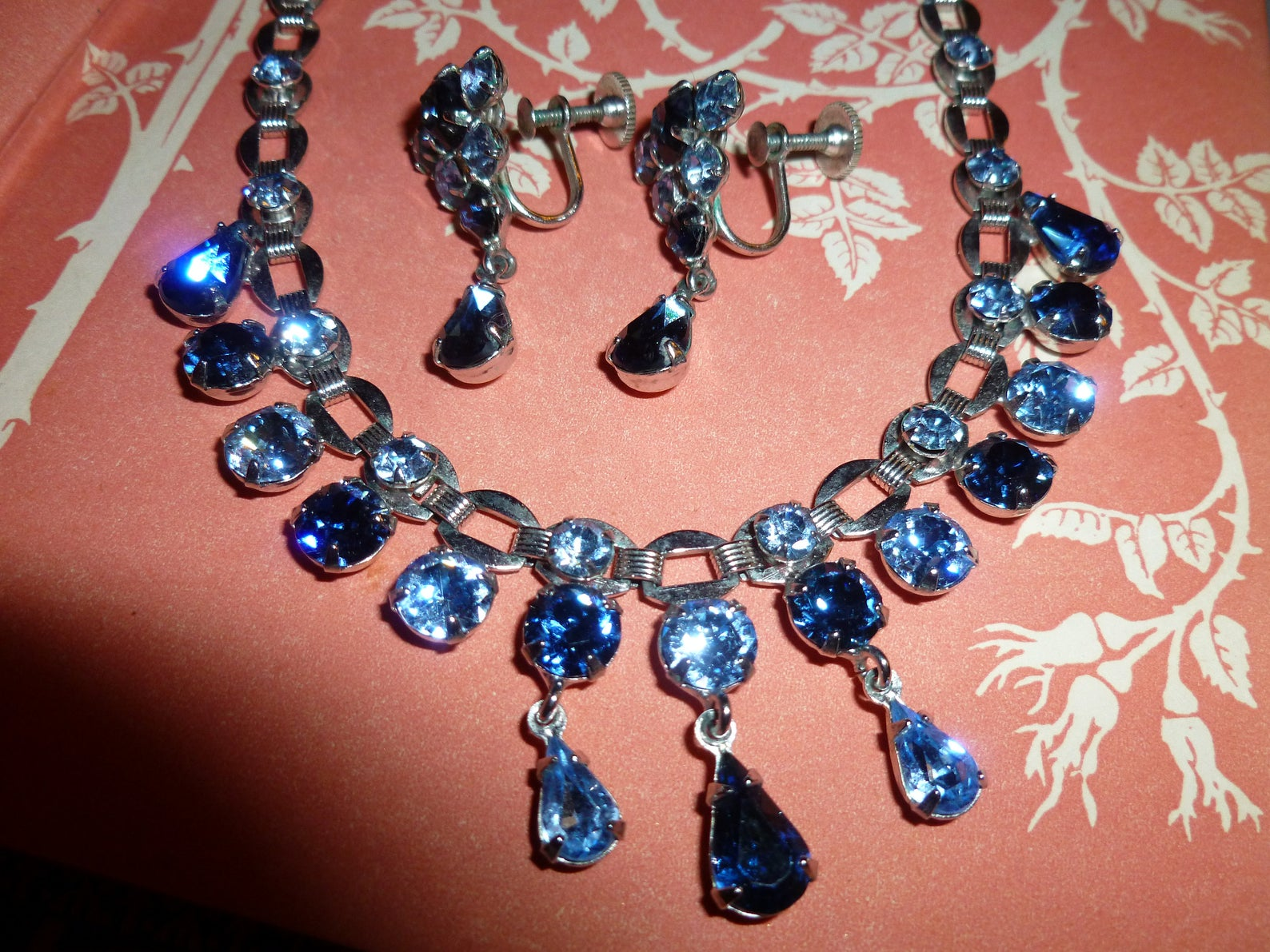 This is a necklace and earring set. Big blue rhinestones are hanging off both the pieces of jewelry.