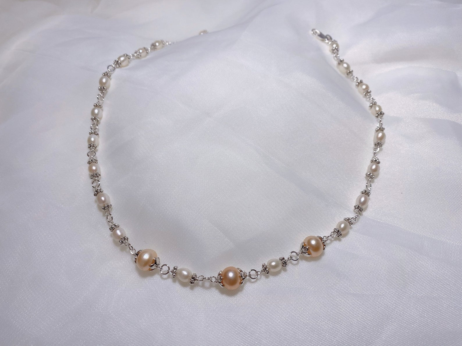 There are three large pearls amongst a sea of smaller white ones, all separated by elegant clasps.