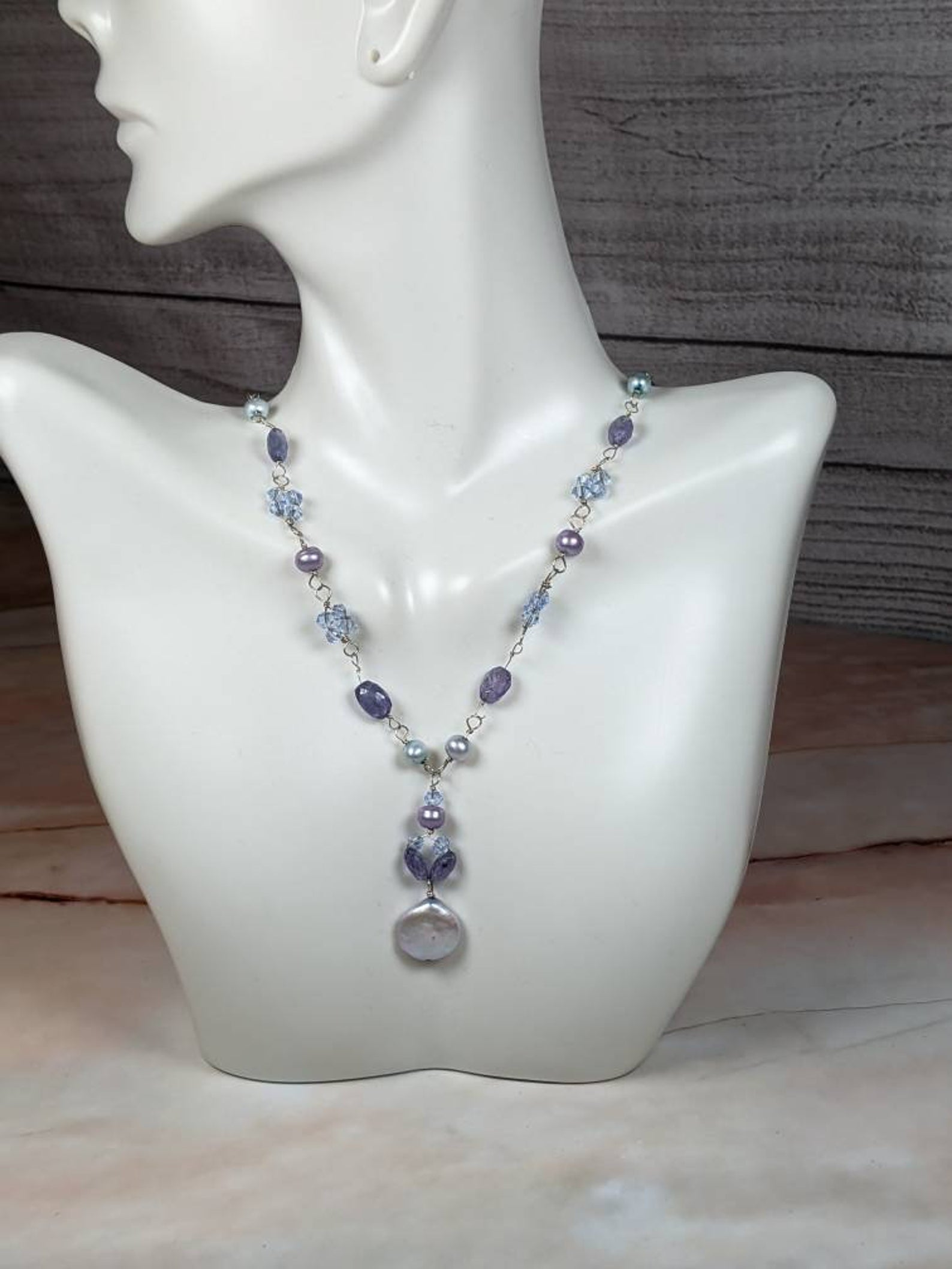 The deep shades of blue and purple bring the necklace a cool ambience. There are jewels and beads assorted in a symmetrical pattern between wire.