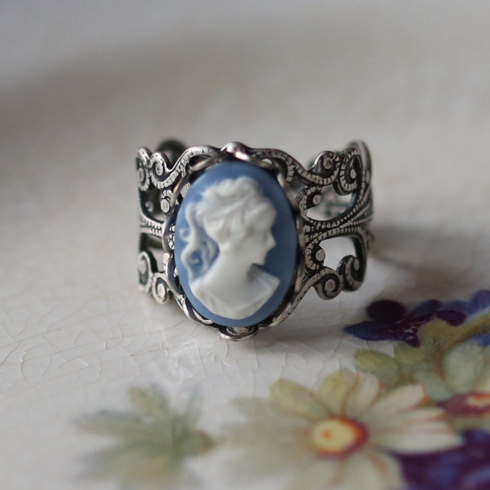 This is a ring. There is a cameo of a lady, which is to say a bust, on a blue drop background. The shank surrounds the size of the backdrop in intricate silver detailing.