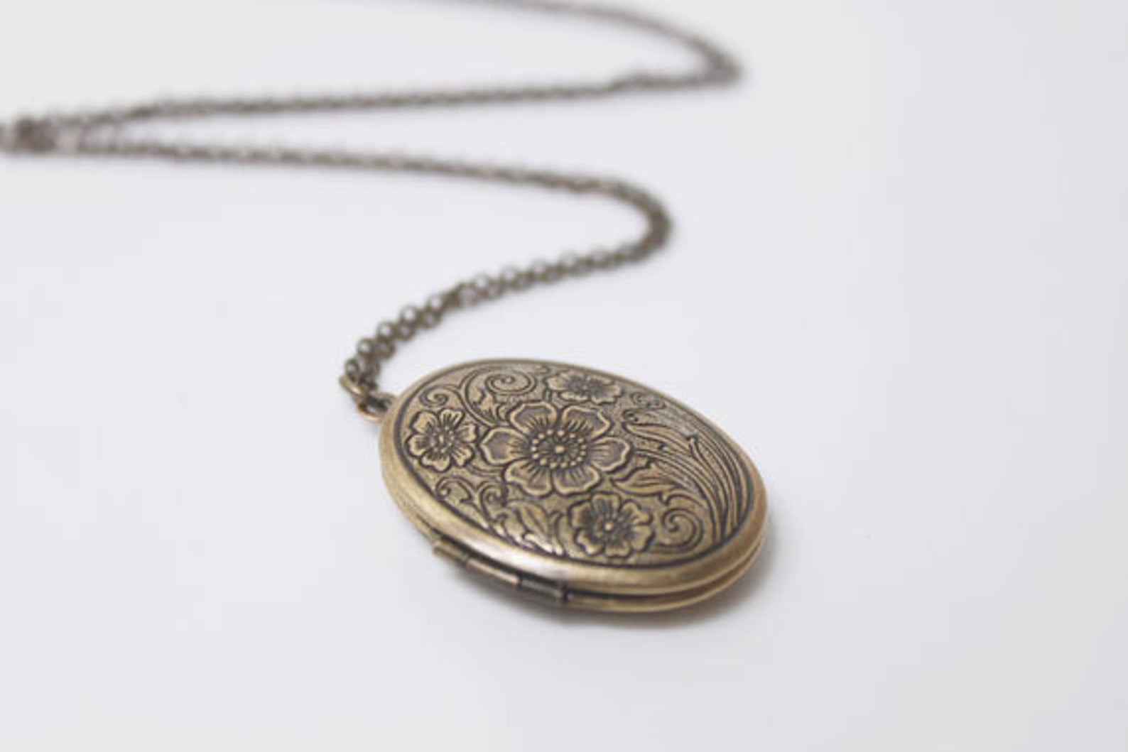 Gold locket necklace with flower etchings.