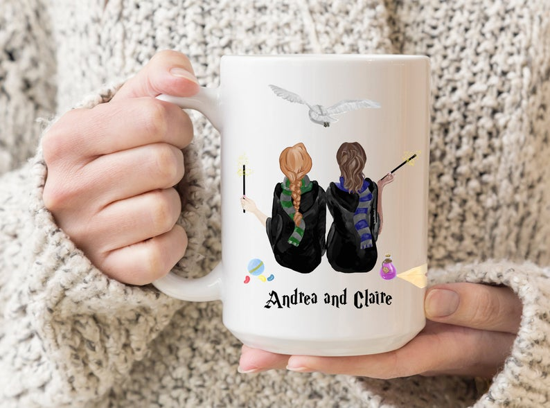 [Image description: a white mug painted with the image from the back of two girls in Hogwarts scarves and holding wands.] via Etsy