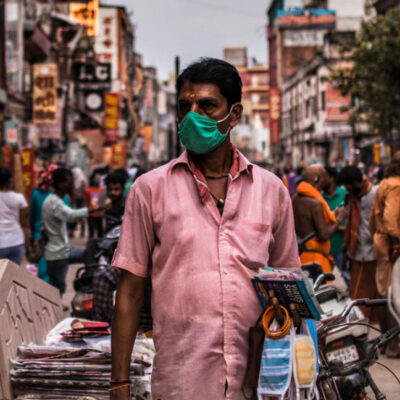 [Image Description: A man wearing a mask is standing in a crowded road in India] Via Unsplash