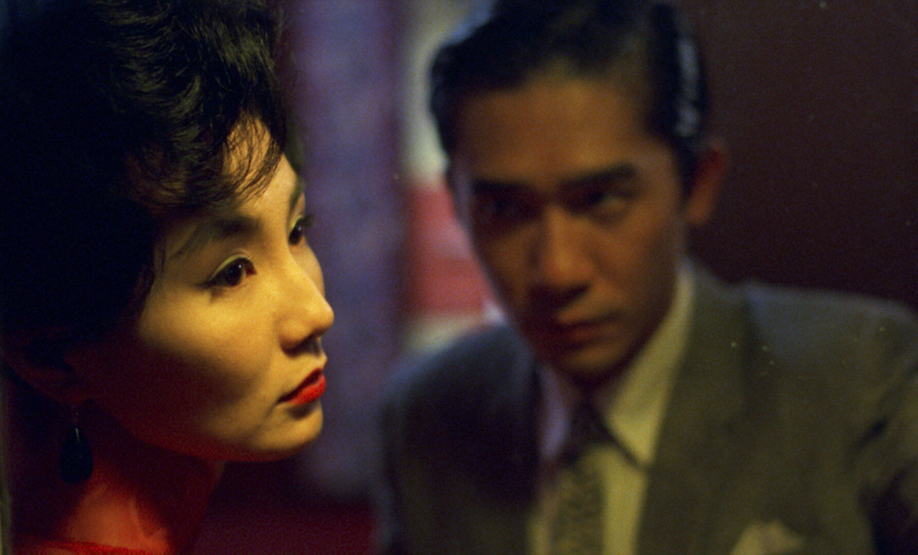 Su (Maggie Cheung) is pictured in the foreground, close, looking forlornly off camera. Chow (Tony Leung Chiu-wai) looks at her but she doesn't notice.