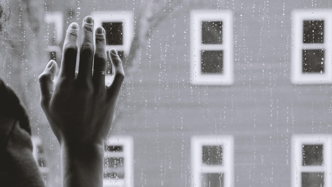 Greyscale image of a women's hand against a window while it rains outside.