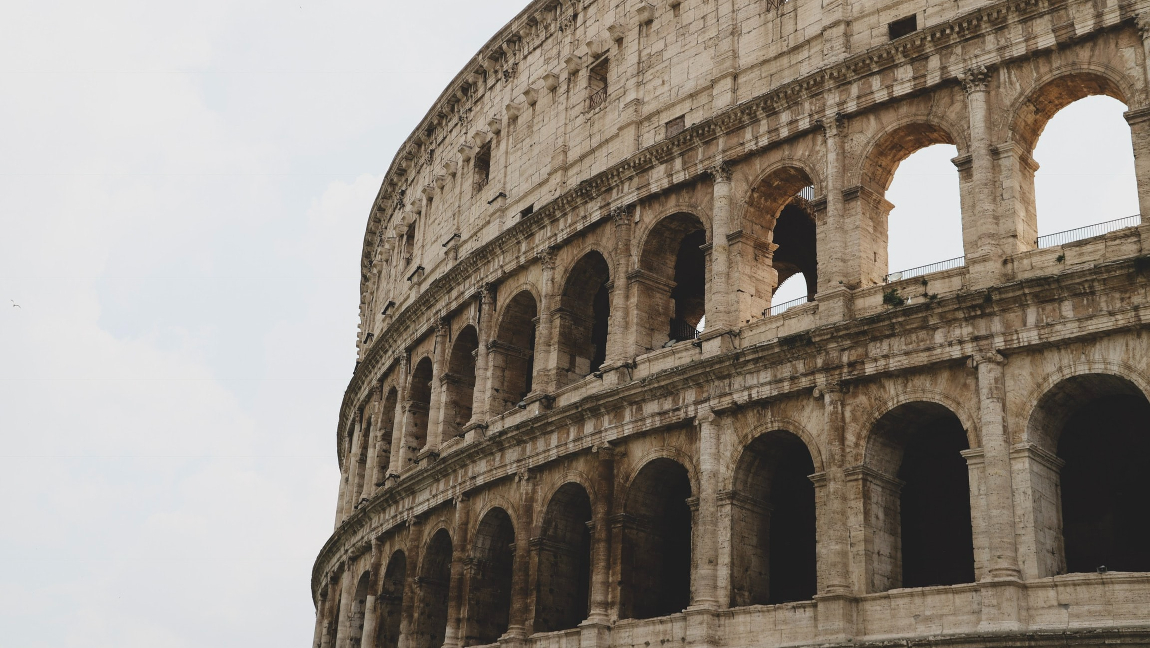 [Image description: The Roman Colosseum stands against a cloudy sky.] Via Unsplash