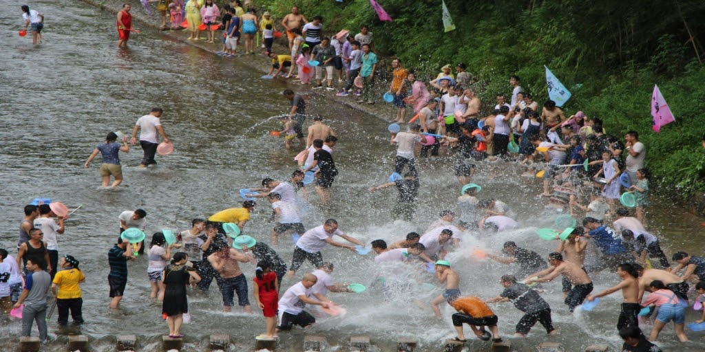 [Image description: People frolicking during the Songkran Water Festival.] Source: laydown on Pixabay.