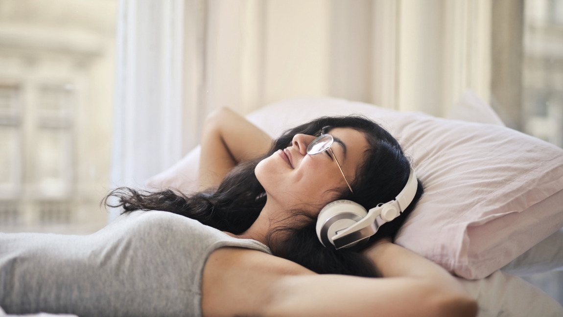 [Image description: Photo of a person laying down on a bed with headphones on.] Via Pexels