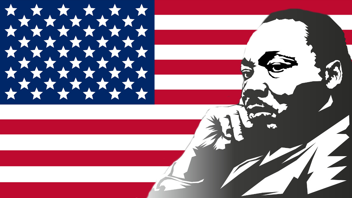 [Image description: Martin Luther King Jr in front of the American flag.] Via Tumisu on Pixabay.