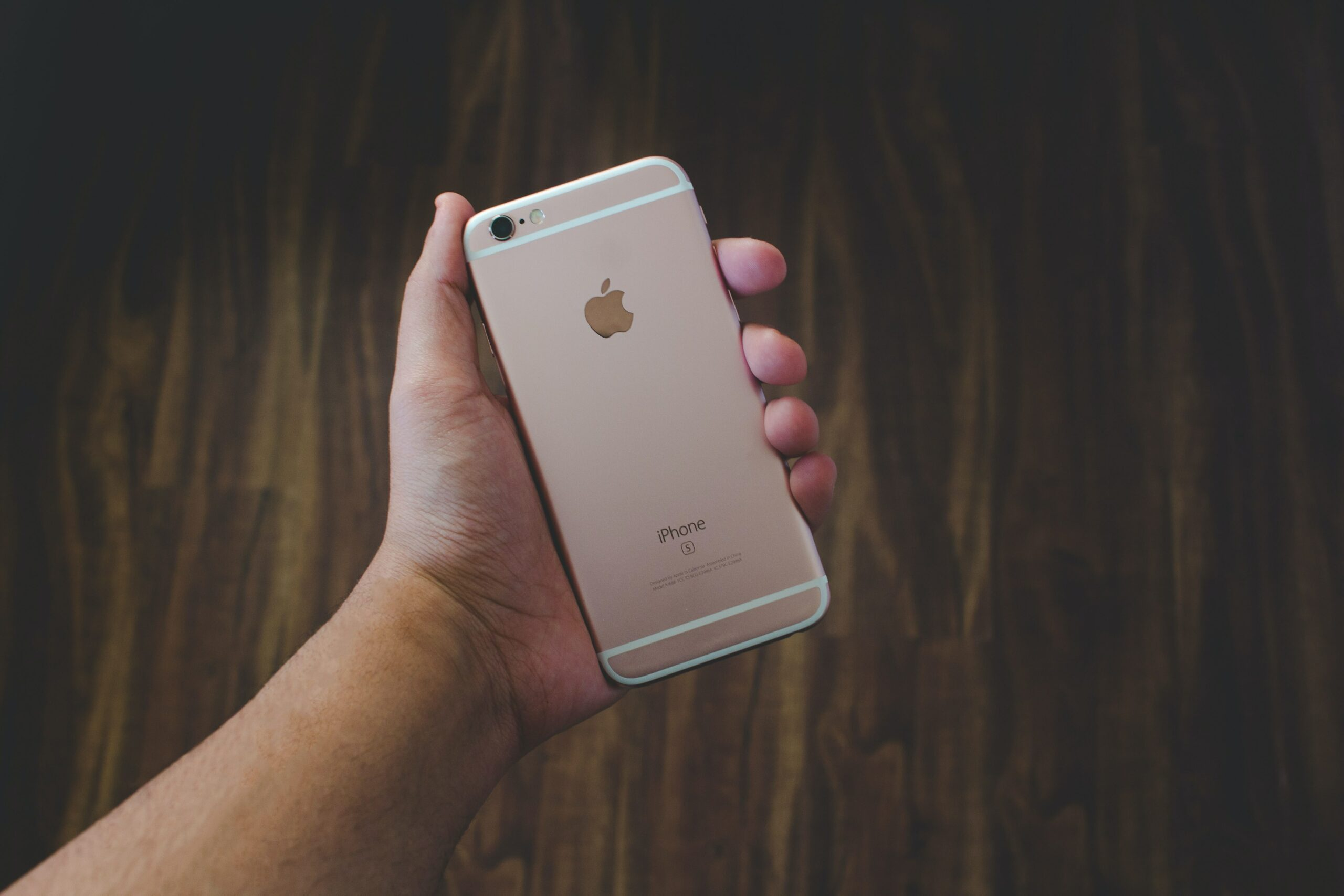 A hand holding a rose gold iPhone 6S.