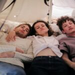 [Image description: Three people lying on a white bed]