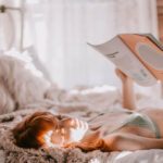 A woman lays on a bed reading a magazine.