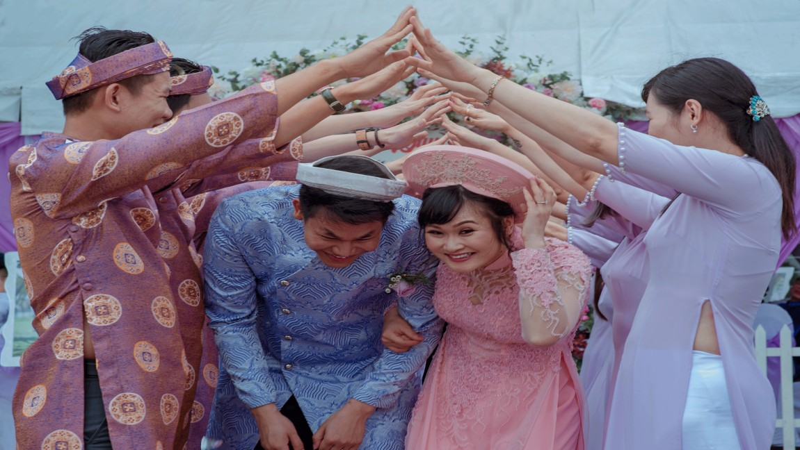[image description: wedding couple taking a traditional ceremony]