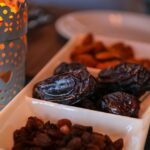 Close-up photo of raisins and dates served in a dish next to a lantern.