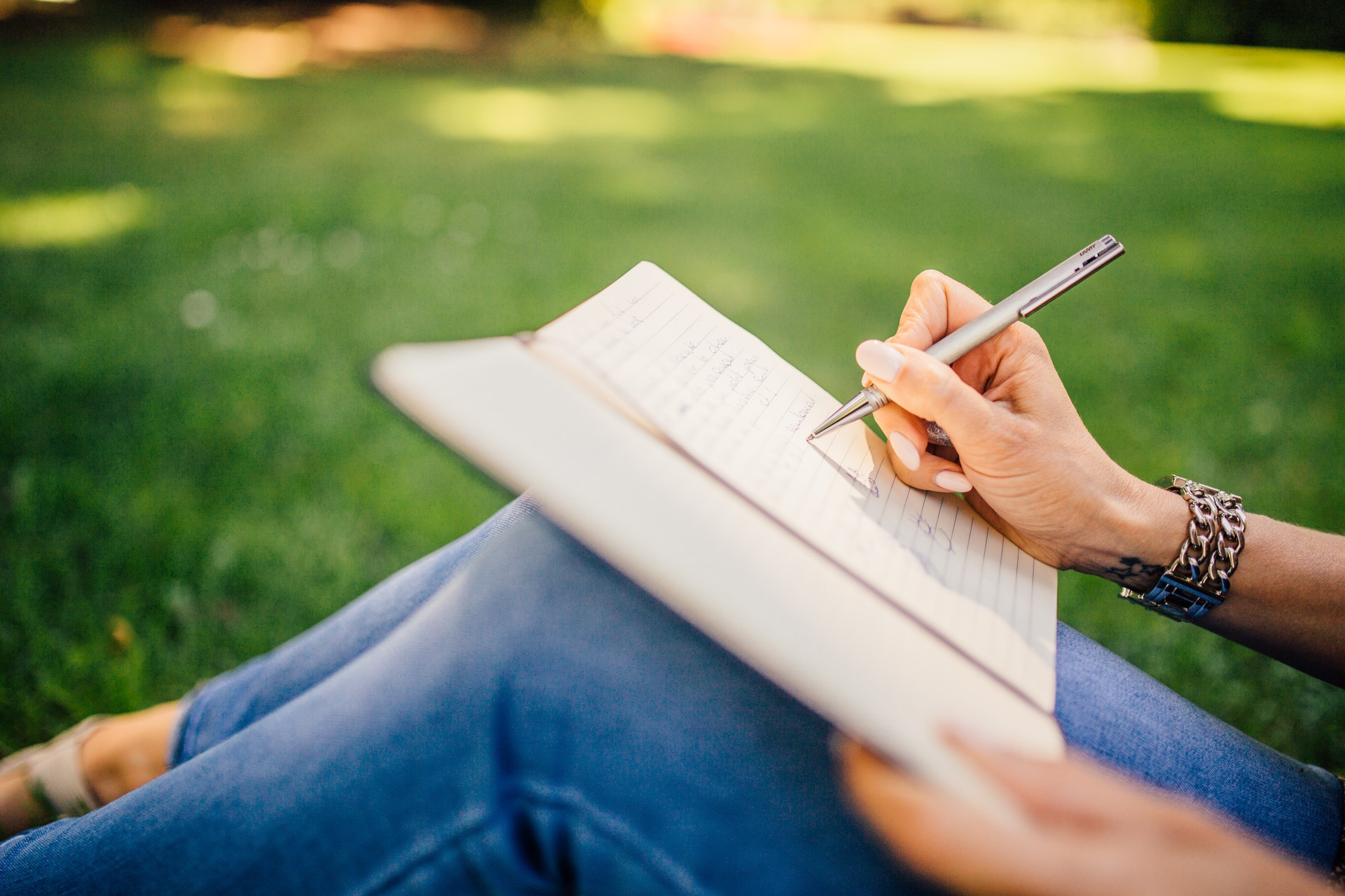 A woman sitting in the grass holding a notebook and pen.