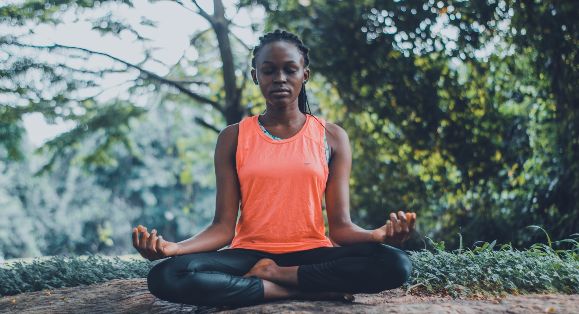 A Black woman with braids wearing an orange top and black yoga pants while mediating outside.