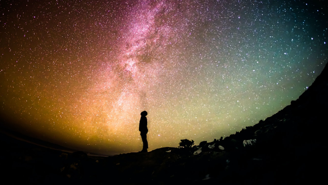 [Image description: A silhouetted figure stares at the night sky.] Via Unsplash