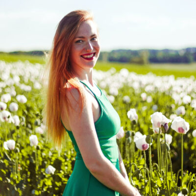 [Image description: A woman in a green dress smiles in a sunny field.] Via Unsplash