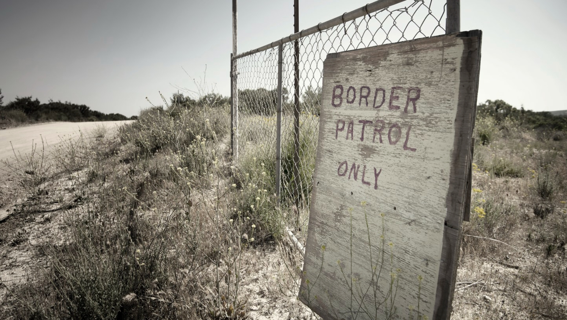 [Image description: Border patrol sign leaning against wire fencing.] Via Unsplash