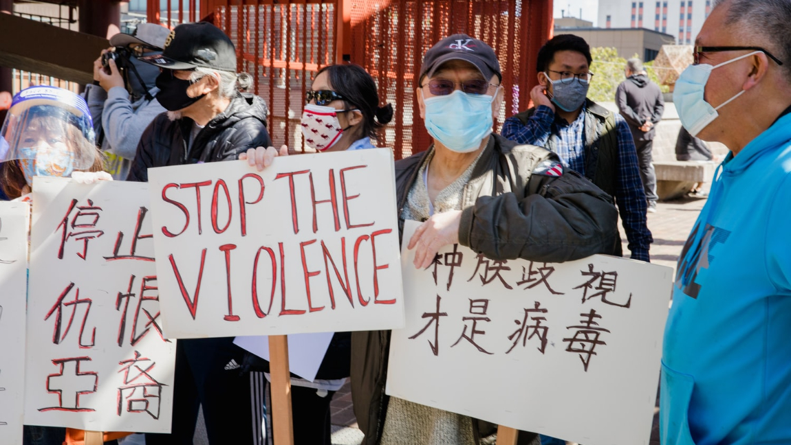 [Image description: Protesters hold up signs against Asian hate.] Via Jason Leung on Unsplash