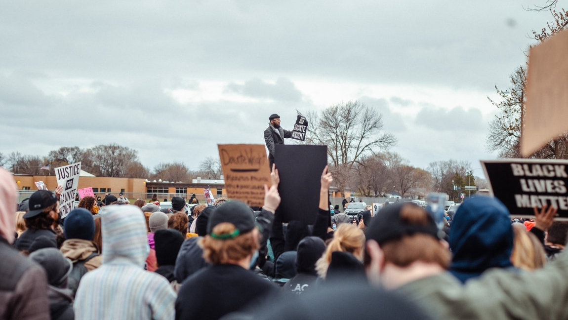 [Image description: BLM protesters gather in Brooklyn Center, MN.] Via Unsplash.