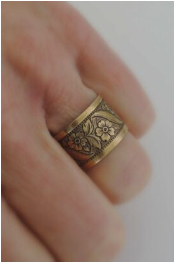 Brass ring with flower engravings around the circumference.