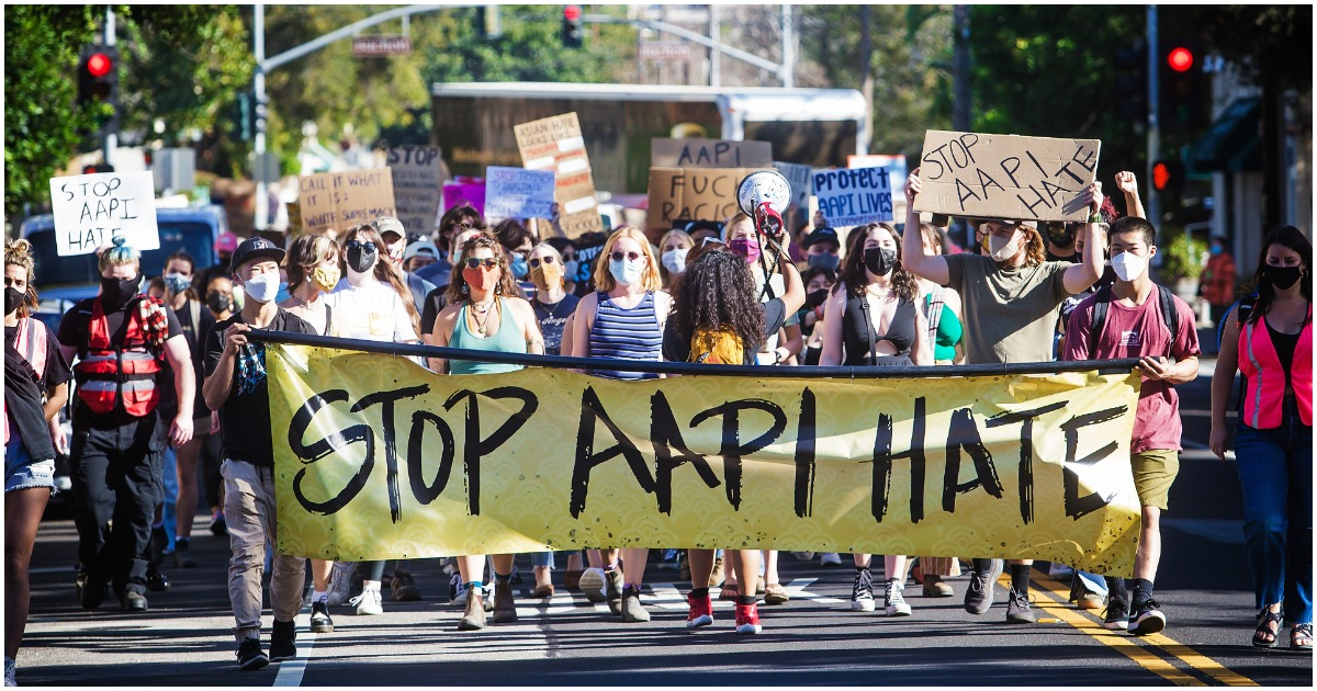 """People line up to march alongside a bright yellow banner that says """"STOP AAPI HATE"""" on behalf of a domestic surge in anti-Asian hate crimes"""