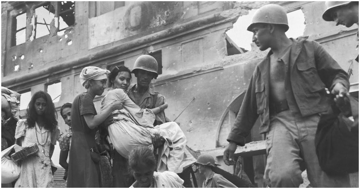 The image is from the Philippines-American War. A soldier helps a Filipina woman down.