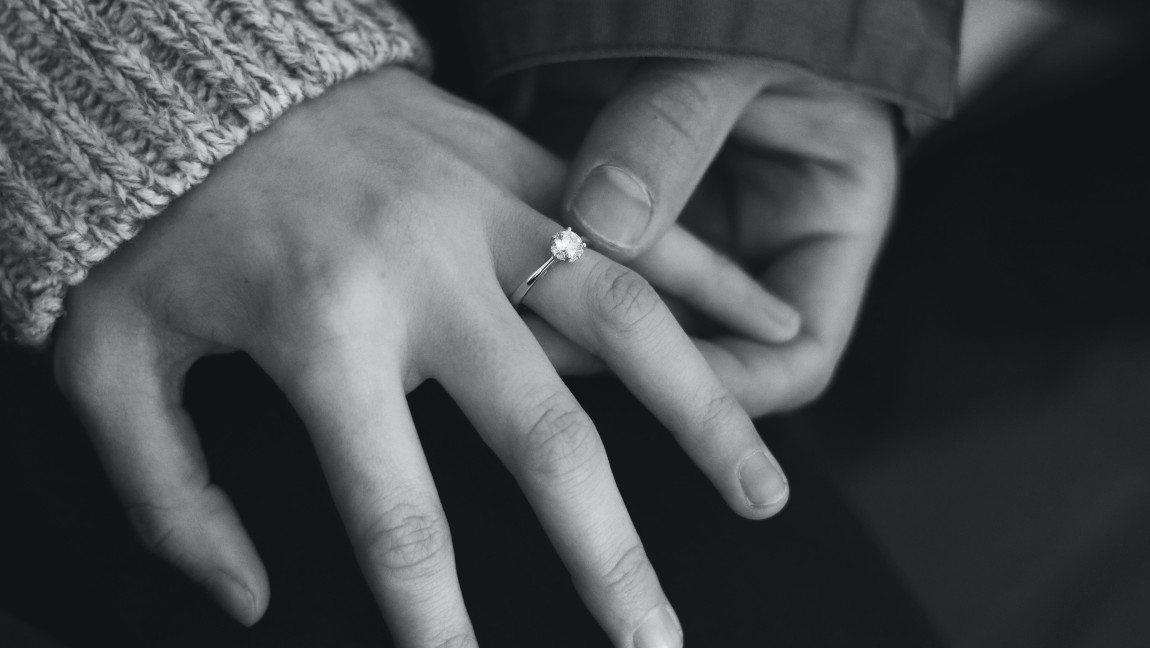 A hand with an engagement ring being held loosely by a larger hand.