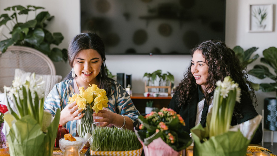 [Image description: Two people sitting at a table and arranging flowers.] Via Pexels