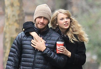 [Image Description: Taylor Swift and Jake Gyllenhall walking around the streets of New York. Taylor has her arm around Jake and they are holding hands while she holds up a coffee.] Via NYT.