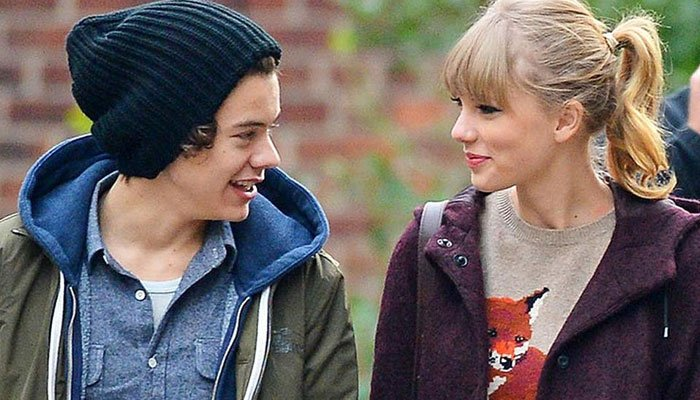 [Image Description: Taylor Swift and Harry styles looking at each other and smiling ] Via GeoTV.