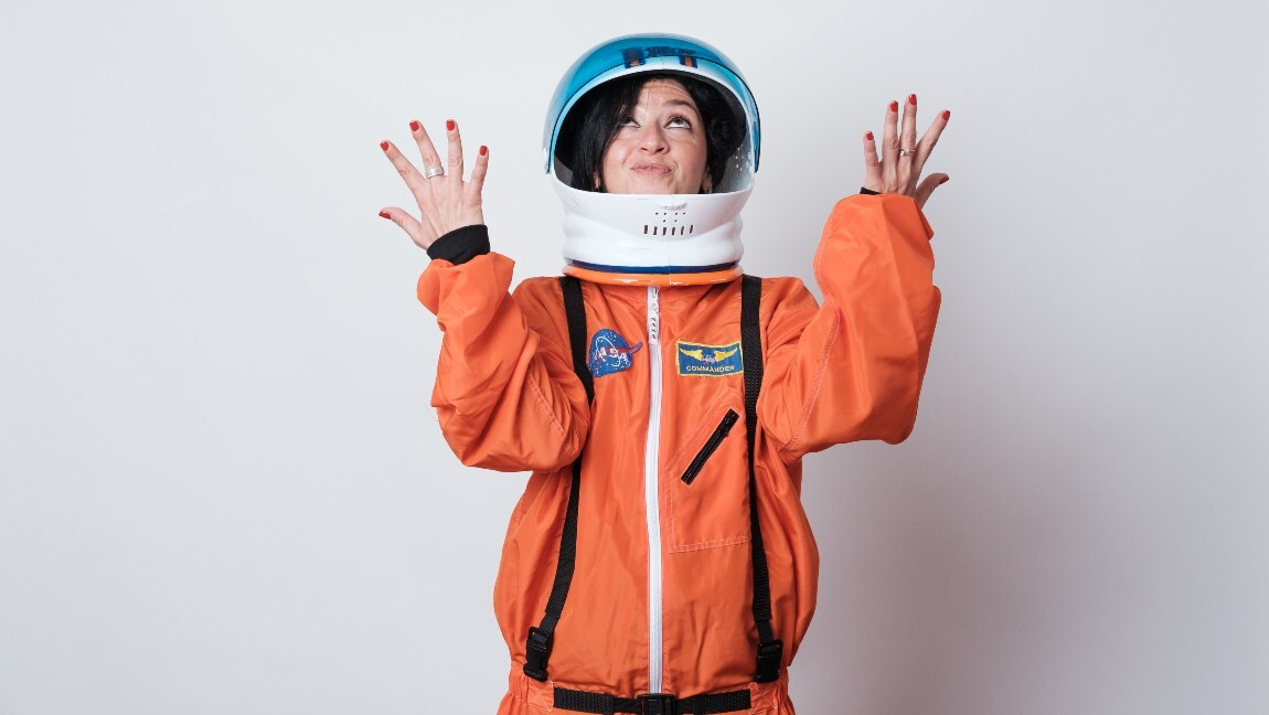[Image description: Eleonora Rocca, founding director of WomenX Impact, wearing an orange astronaut suit] Via Eleonora Rocca