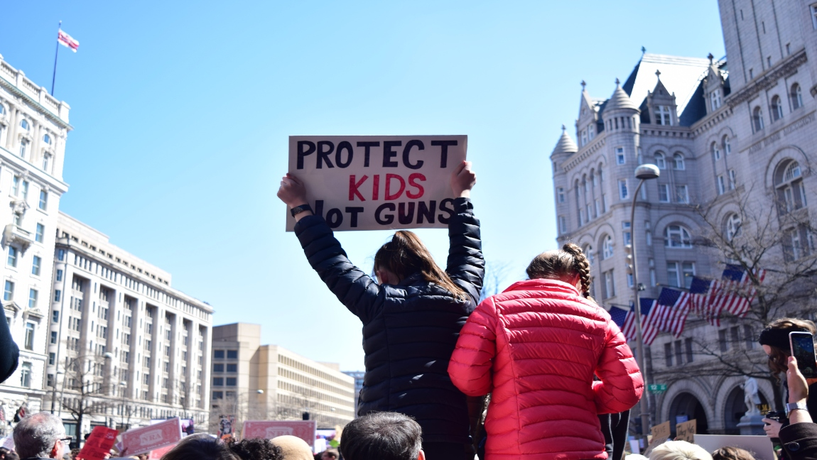 """A person holds up a sign that reads, """"Protect kids not guns"""""""