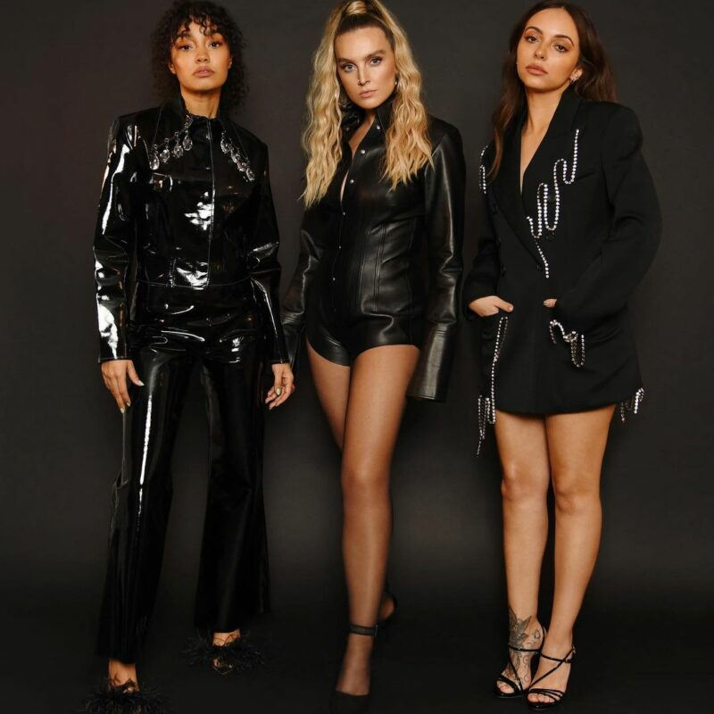 Image Description: (left to right) Leigh-Anne Pinnock, Perrie Edwards and Jade Thirlwall of Little Mix all stood dressed in black.