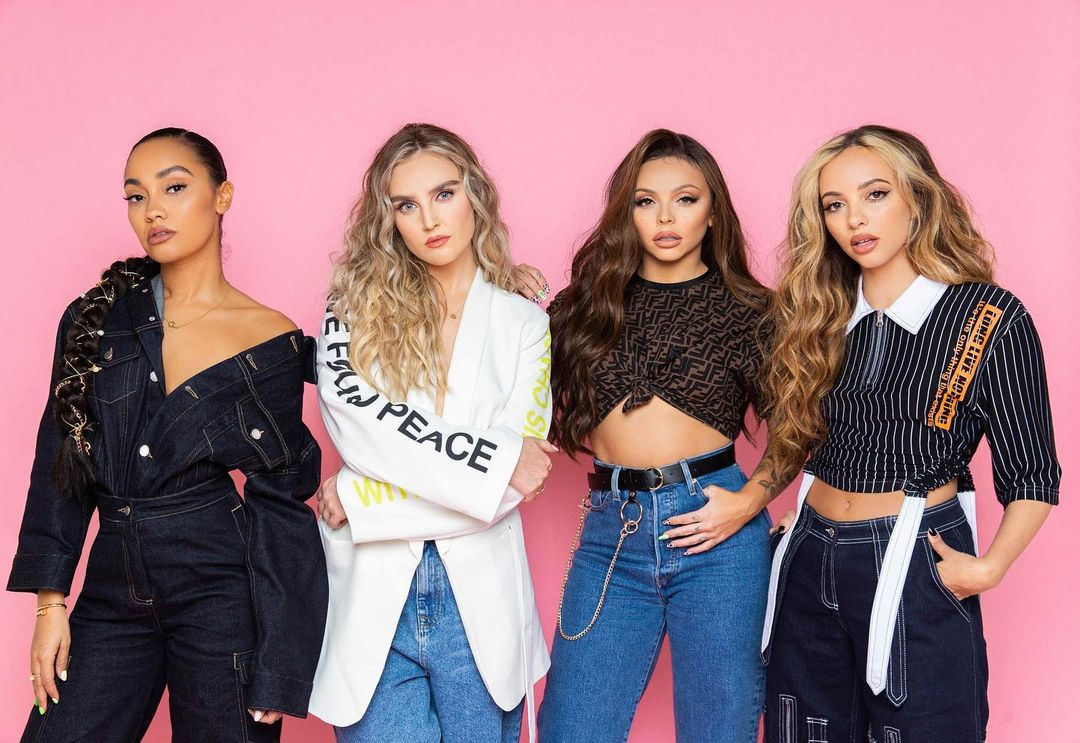 Image Description: (left to right) Leigh-Anne Pinnock, Perrie Edwards, Jesy Nelson and Jade Thirlwall of Little Mix stood against pink background