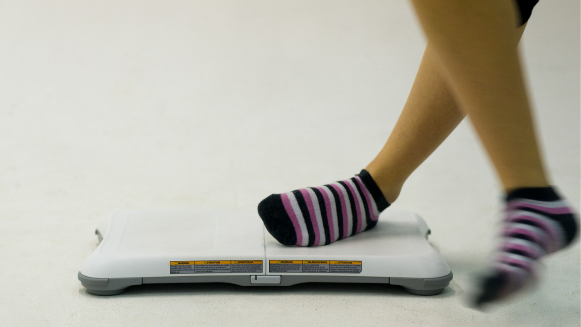 A young person with stripy socks stepping off the Nintendo Wii Fit balance board.