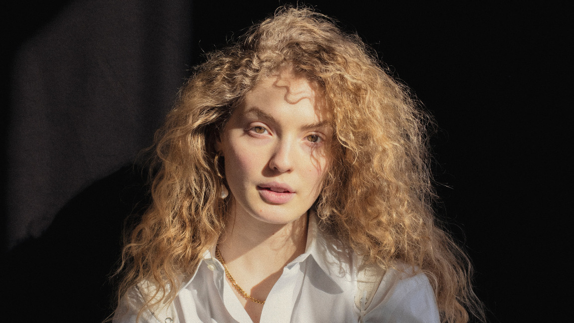 Young woman with dark blonde curly hair in a white shirt and corset