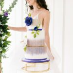 A women in a wedding dress standing behind a wedding cake with purple flowers.