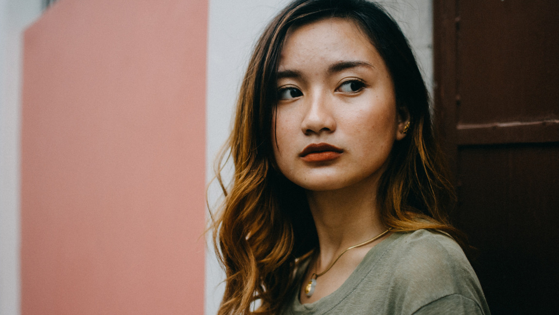 [Image description: Photo of a woman against a pink and white wall.] Via Pexels