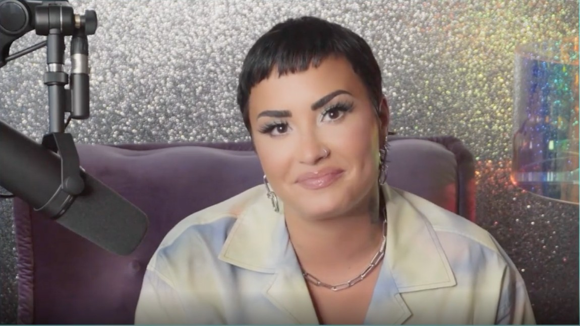 [Image description: a brunette person, Demi Lovato, sitting in front of a microphone, smiling]