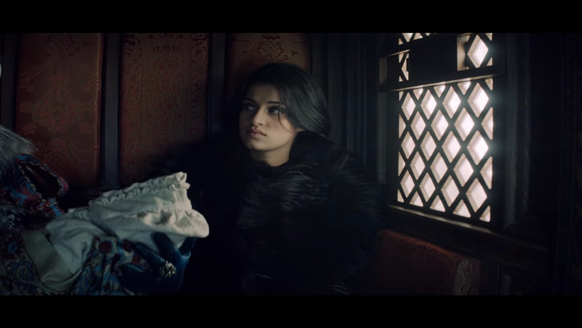 [image description: a dark haired woman, Anya Cholatra, in a carriage]