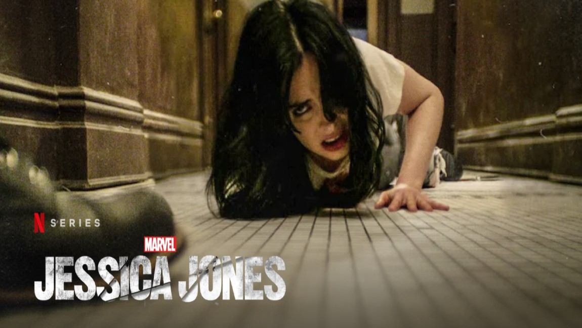 [image description: a dark haired woman, Krysten Ritter, in white crawling on a tile floor and text reading N series Jessica Jones]