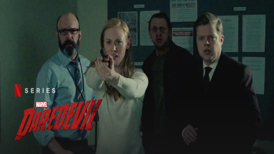 [image description: a group of people standing together, with a blonde woman holding a gun and text reading N series Daredevil]