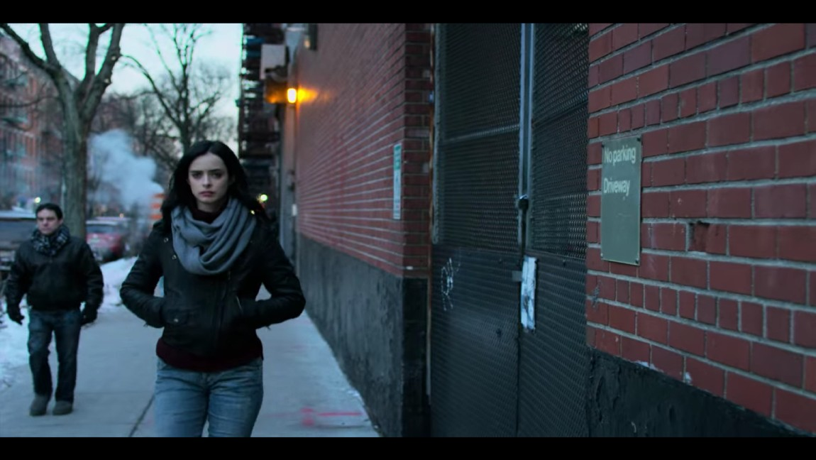 [image description: a woman with black hair and a leather jacket and jeans walking down a sidewalk near a brick building]