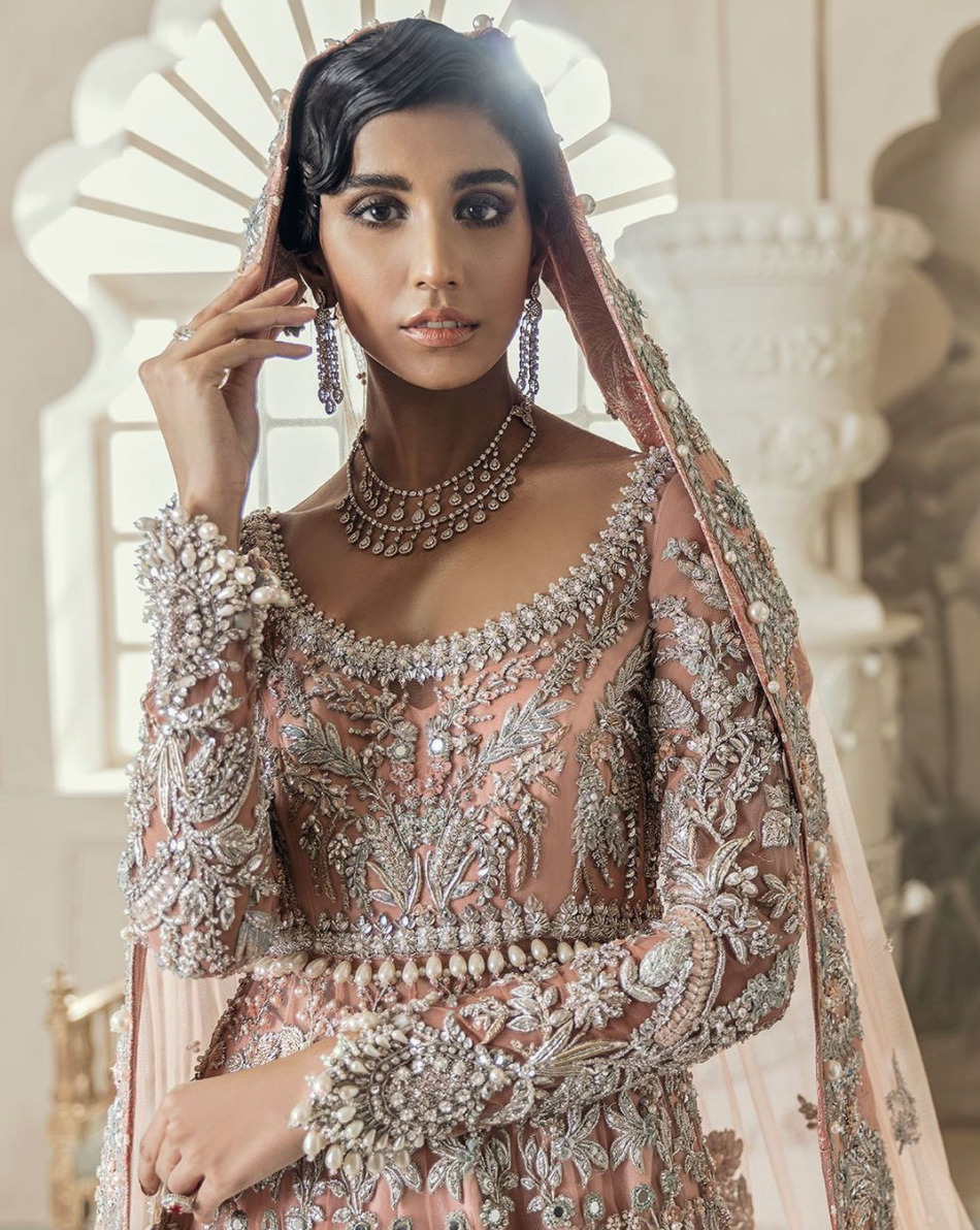 Image of a woman wearing traditional, South Asian bridal wear by fashion designer Élan. A blush pink dress with silver embellishments.