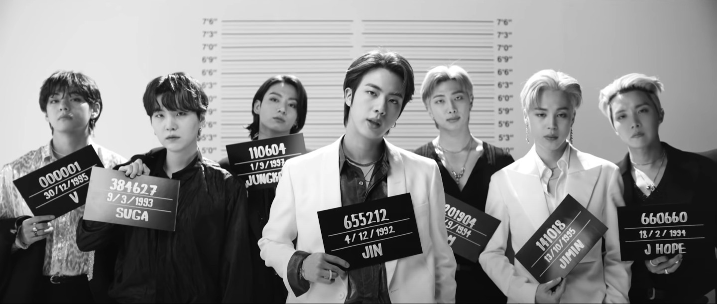 [Image Description: BTS posing mug shot style in a black and white still] Source: Youtube