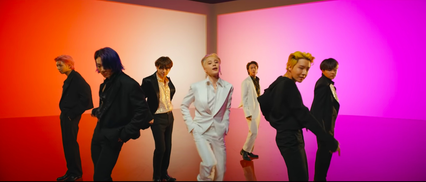 [Image description: BTS dancing in retro outfits in front of an orange and purple background] Source: Youtube